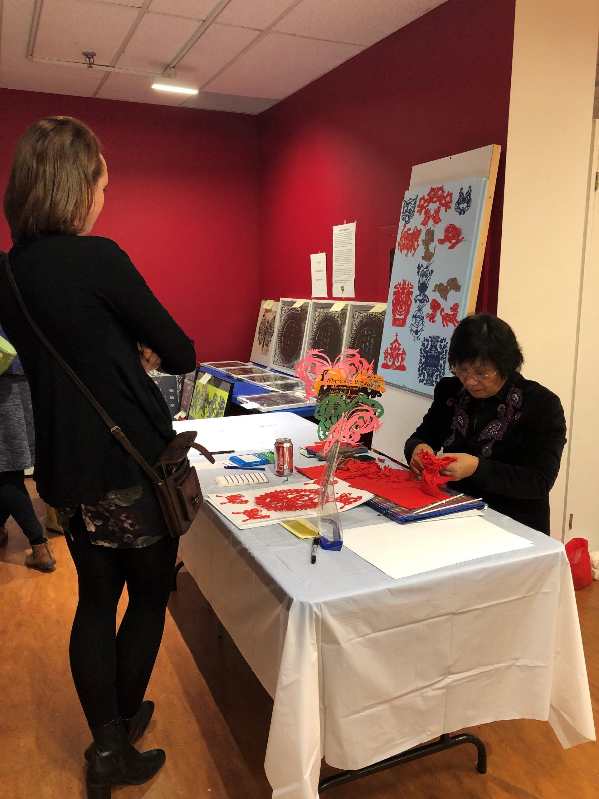 Paper Cutting artist Xiqin Li, creating a custom piece for volunteer Erinn